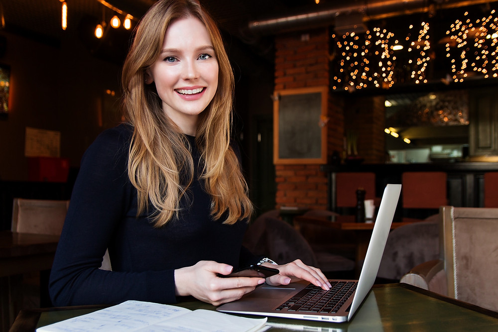 Pretty red-haired young woman working on a laptop and smiling.