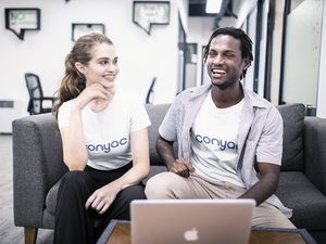 White woman and black man wearing Conyac t-shirts and looking at a MacBook Pro.