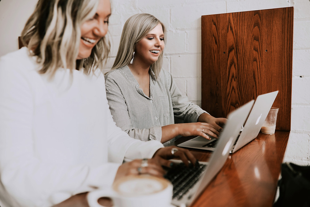 Two blonde women working together on MacBook Pros in a cafe.