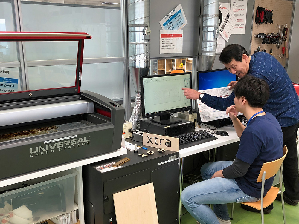 Japanese men planning laser cutting project, Tokyo, Japan