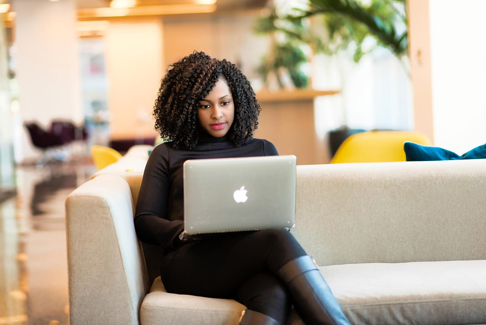 Black woman with dreadlocks working on a MacBook Pro - photo by Christina Morillo via Pexels