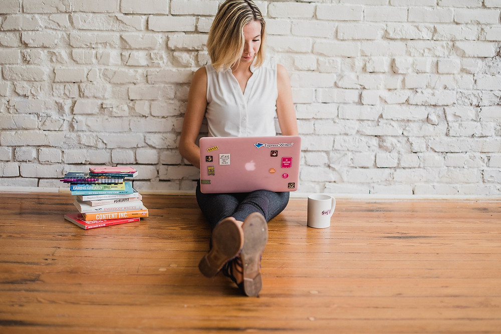 Blonde woman sitting on wooden floor and using MacBook Pro with pink laptop cover.