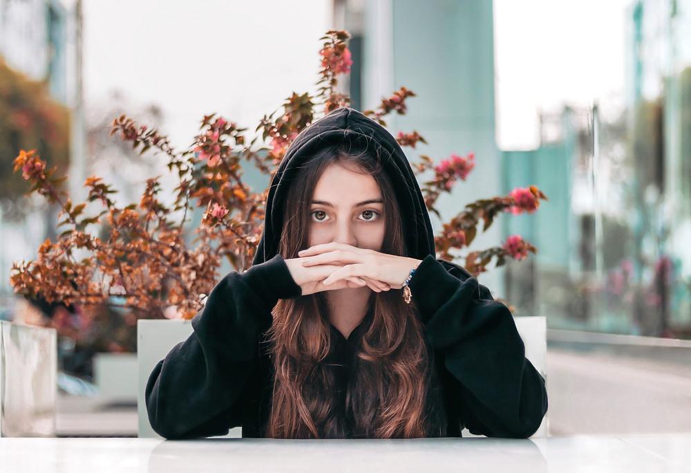 Pretty young brunette woman wearing black hoodie.