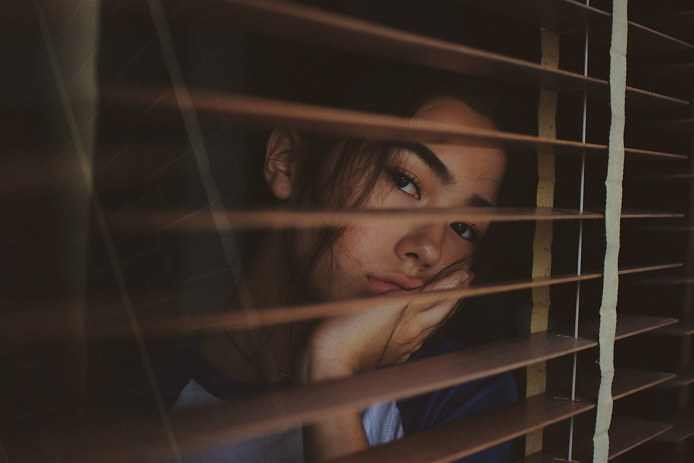 Pretty young Asian woman looking through blinds