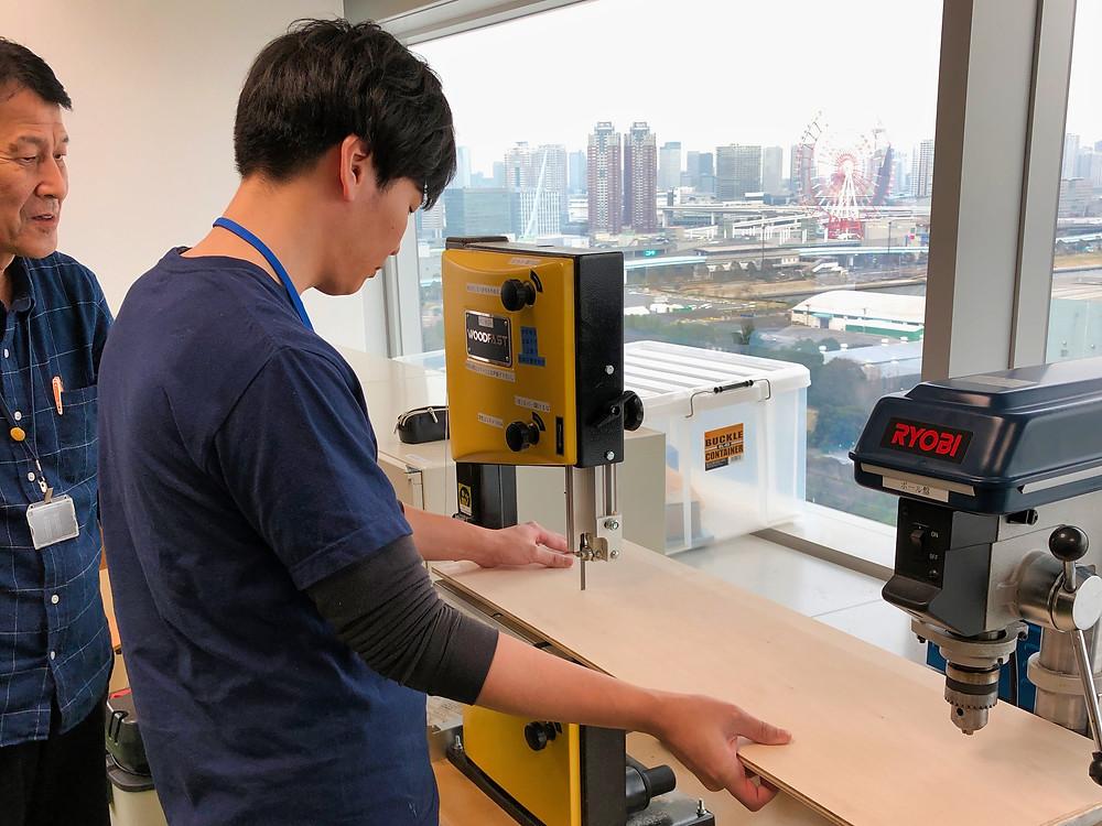 Japanese men using laser cutter, Tokyo, Japan