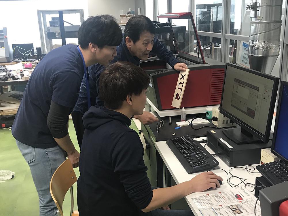 Japanese men planning laser cutting, Tokyo, Japan