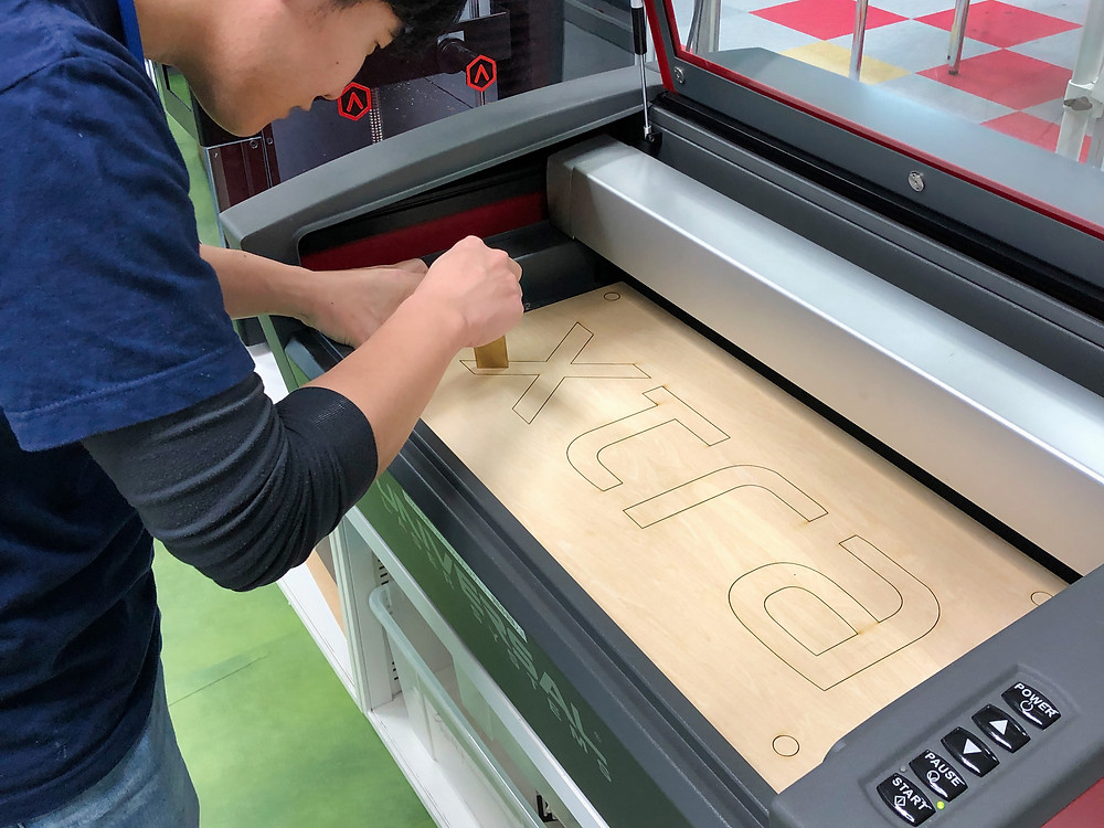 Japanese man cutting corporate logo from wood, Tokyo, Japan