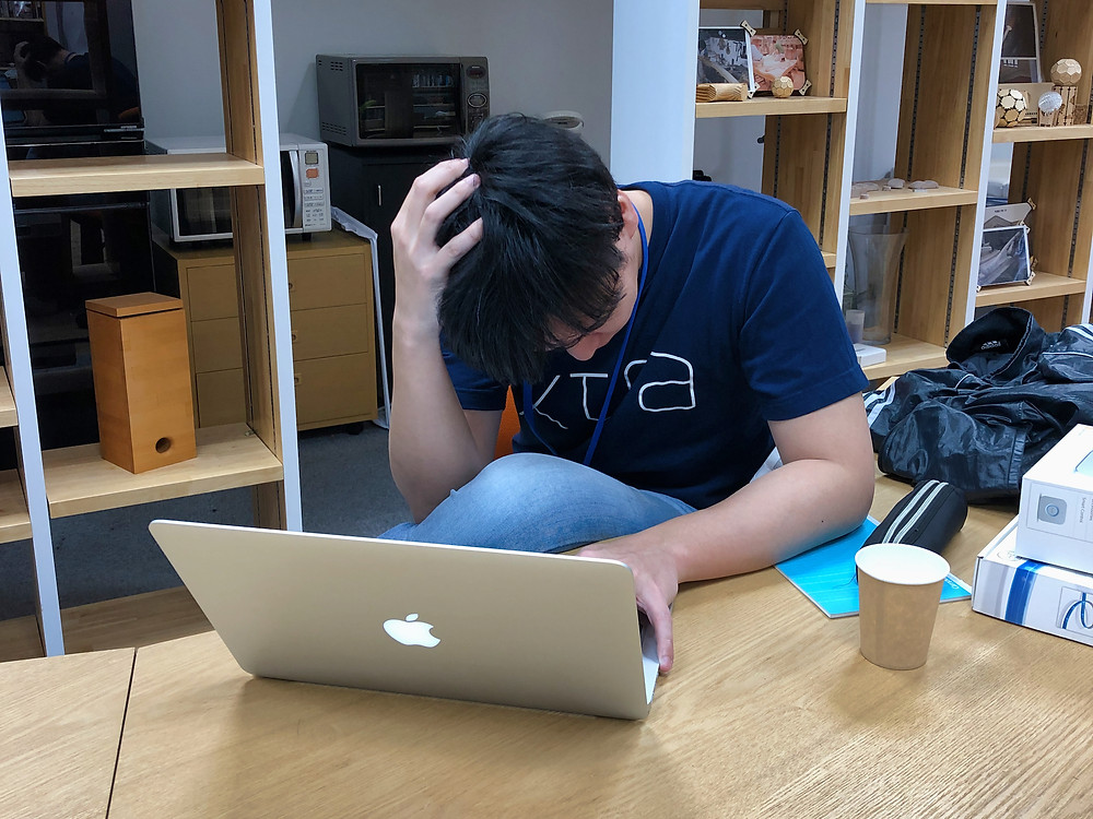 Japanese man thinking with MacBook Pro