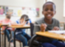 Disabled pupil smiling at camera in clas