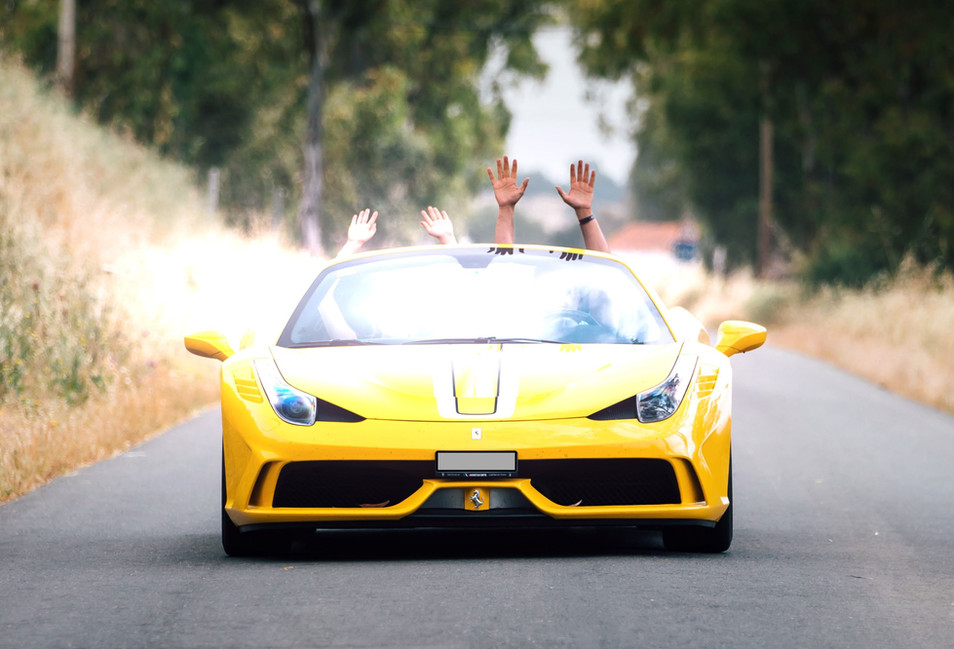 happy couple driving in a Ferrari convertible in Tuscany