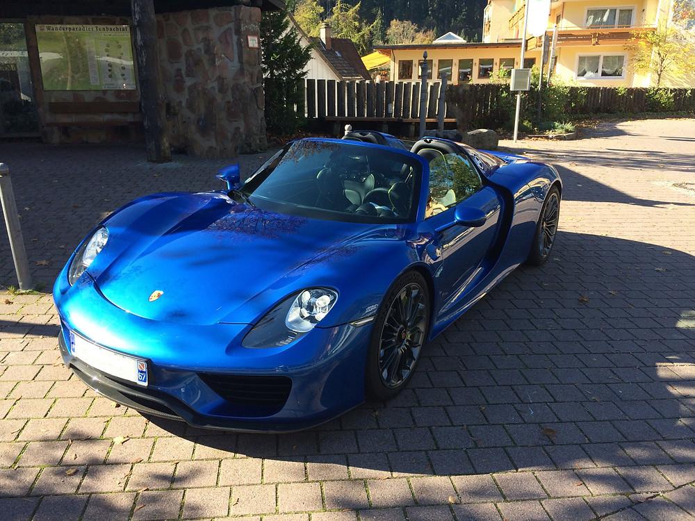 blue Porsche 918 Spyder parked in the shadow