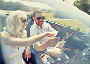 couple sitting in convertible on road trip looking at a map