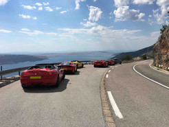 supercars parked on scenic road wioth Sea view