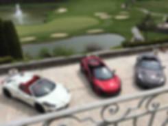 Ferrari, Aston Martin and McLaren supercars parked next to golf course