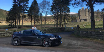 Man posing with Jaguar F Type at castle in Scotland