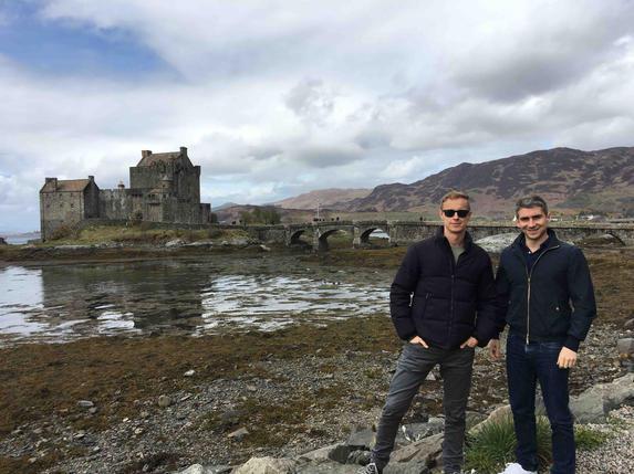 Two men posing in front of bridge to Eilan Donan Castle