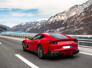 Ferrari driving scenic road by lake in the Swiss Alps