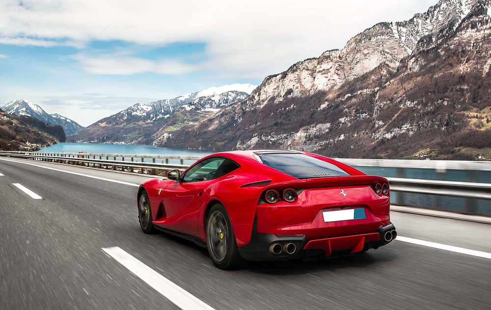 red Ferrari driving on a Road Trip in the Swiss Alps