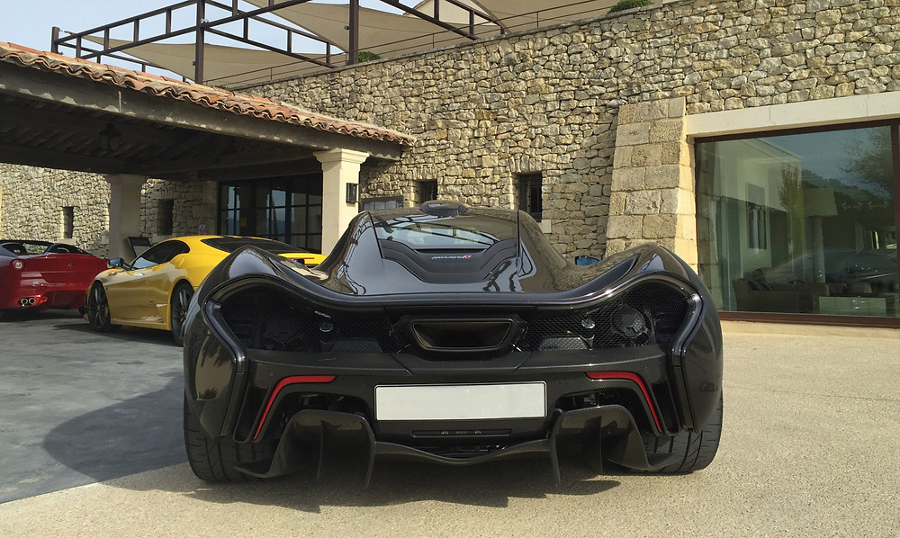 rear of McLaren P1 parked in front of two Ferrari