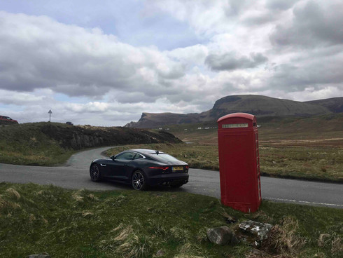 Jaguar F Type parked next to red British phone booth on the Isle of Skye in Scotlanf