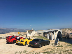 Supercars parked next to iconic Pag Island Bridge