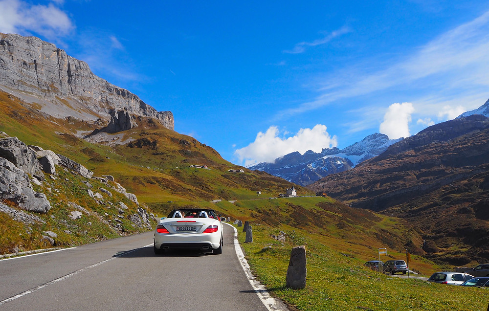 Mercedes roadster driving on Klausen Pass in the Swiss Alps