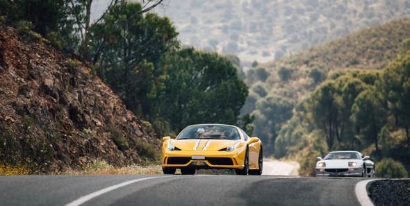 Couple in Ferrari driving through Tuscany