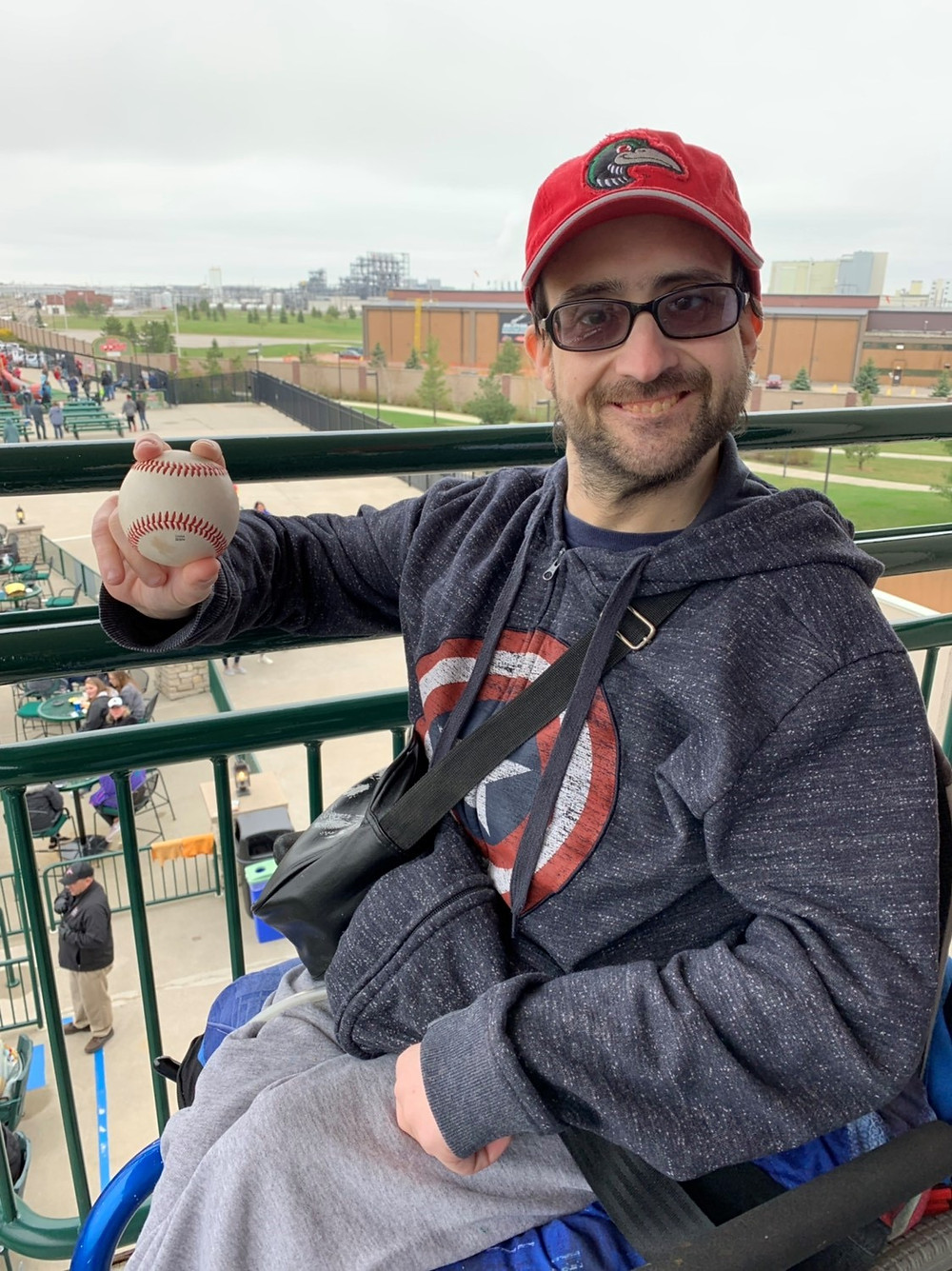 DNMM consumer holding baseball at Great Lakes Loons baseball game