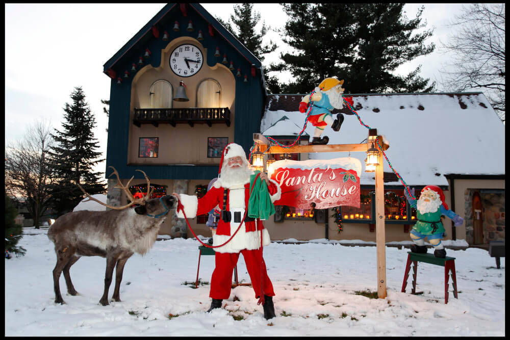 Santa and a reindeer outside the Midland Santa House