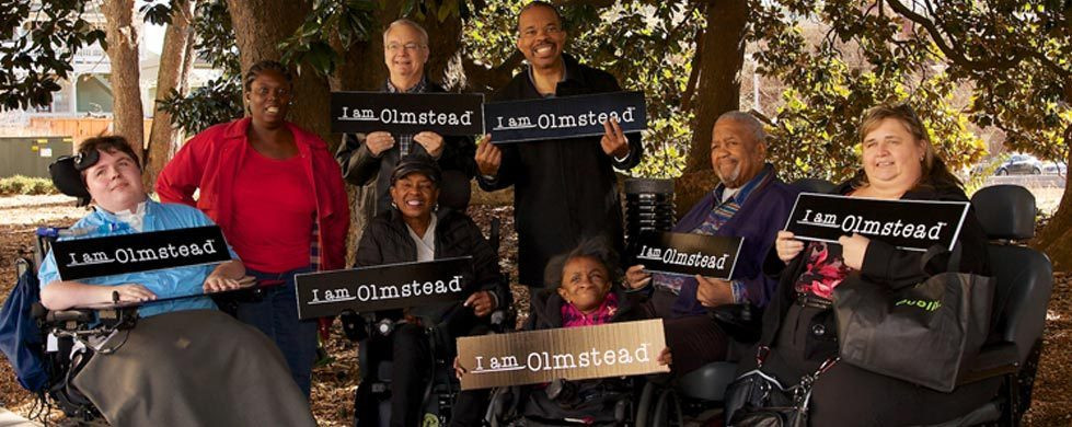 8 people standing in park holding I Am Olmstead signs