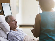 woman advocate speaking with a male hospital patient