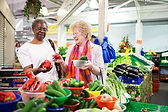 Woman and female assistant grocery shopping