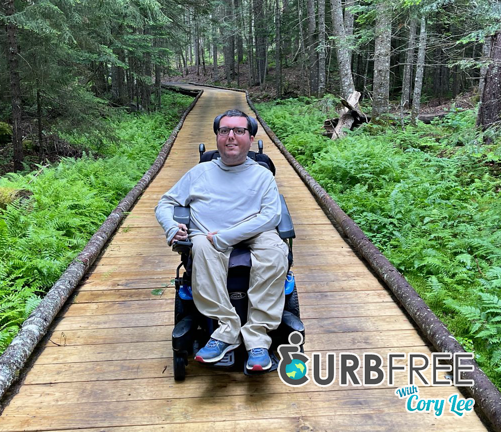 blogger cory lee on wheelchair accessible path  through michigan forest