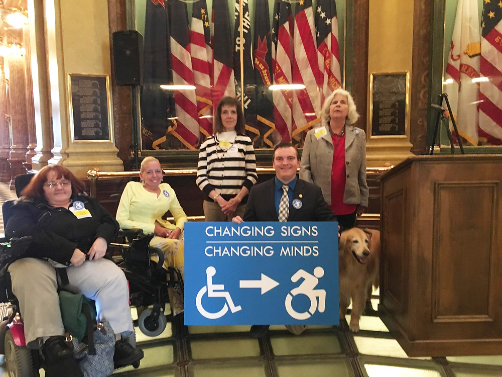 """DNMM executive director Kelly PeLong with two board members and a volunteer, meeting in capitol rotunda with Representative LaFaive in support of his bill changing the accessibility logo to the updated """"go"""" logo showing a wheelchair in motion"""