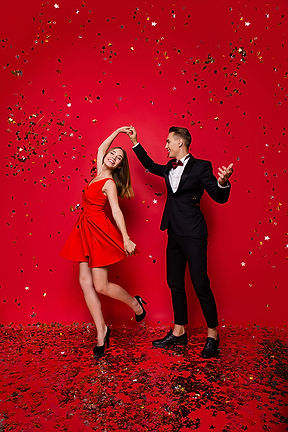 woman in red dress dancing with man in black tuxedo with fancy red backdrop