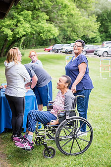 Woman using wheelchair and her support coordinator attend a community picnic