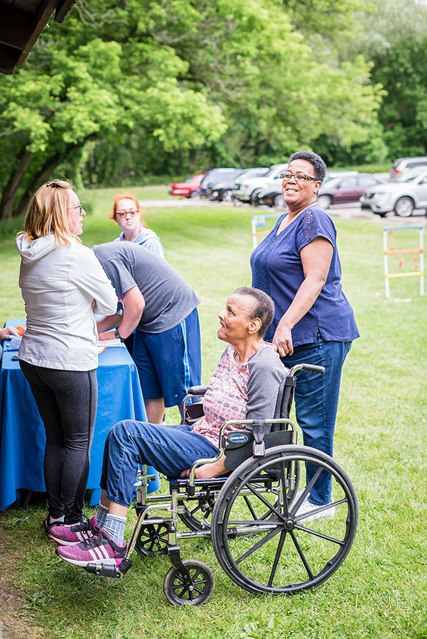 Wheelchair user and staff attending a picnic