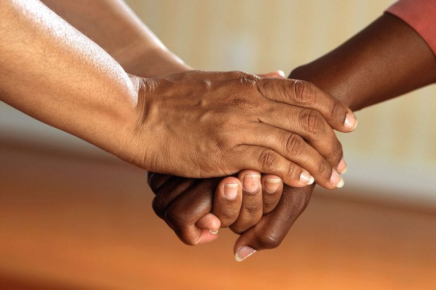 image of two hands clasping each other in support