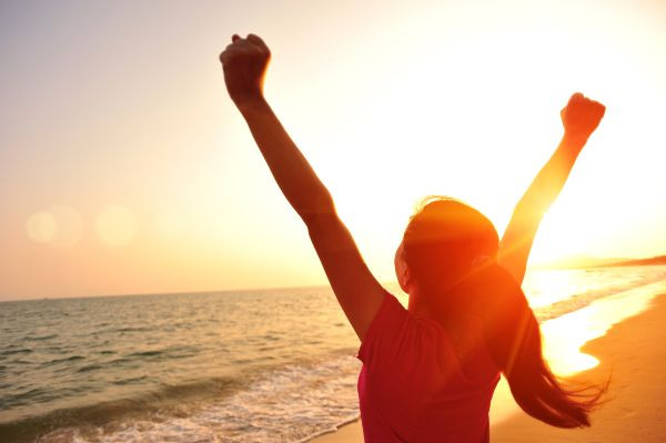 Girl at beach with arms raised in triumph, with setting sun