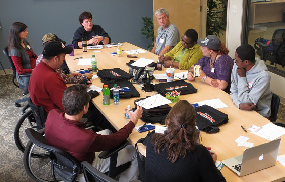 people sitting at table for training, different races, some with disabilities