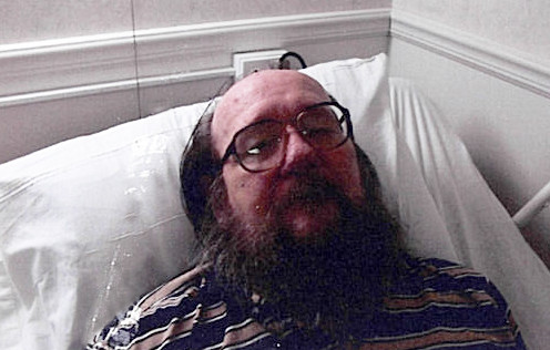 man lying in hospital bed looking unhappy