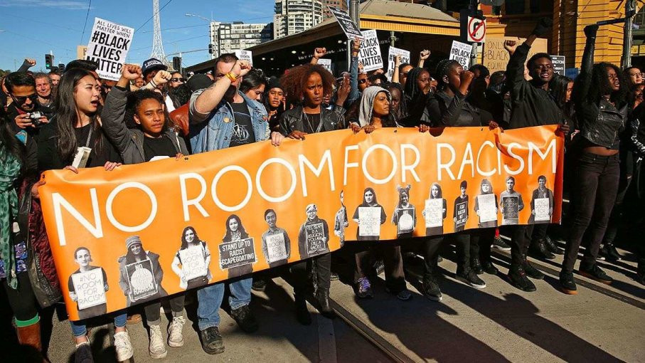 Protest marchers during black lives matter rally with sign reading no room for racism