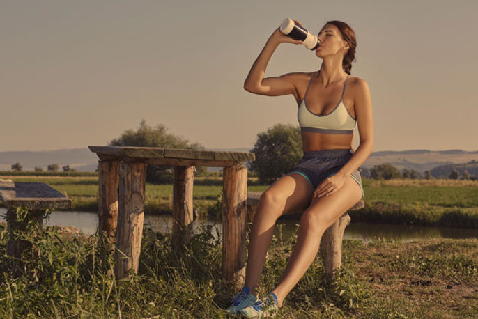 A fit, athletic woman drinking from a water bottle during a workout.