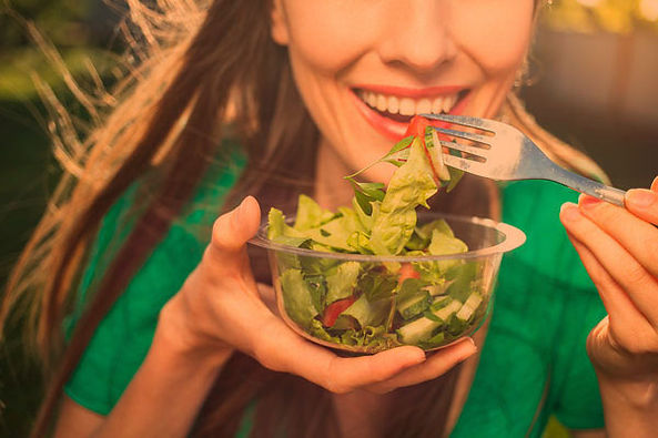 A woman eating a salad and healty food