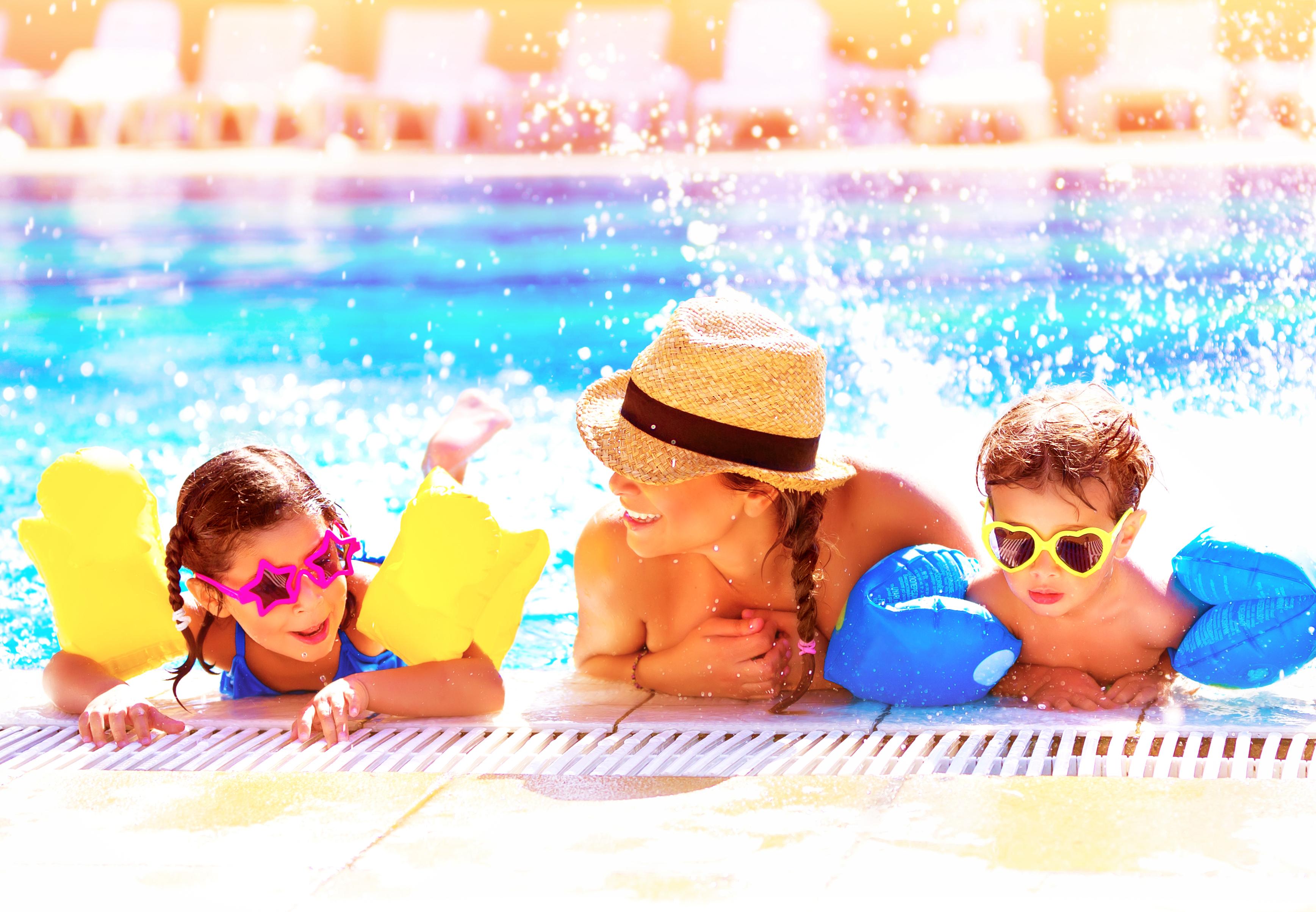 Portrait of happy cheerful family having fun in aquapark, swimming in the pool,