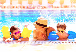 Portrait of happy cheerful family having fun in aquapark, swimming in the pool,