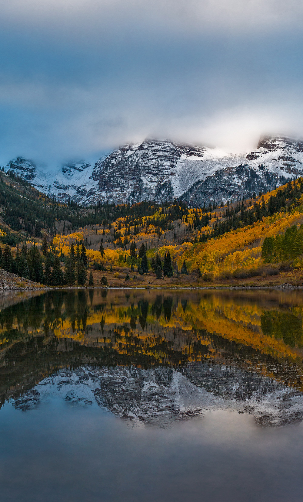 A cloudy morning reflection of the Maroon Bells over Maroon Lake in Aspen, Colorado