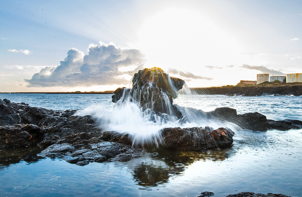 A wave crashes over a rock in Kauai as the sun sets behind it.