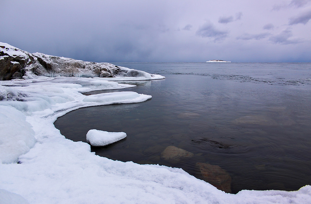 The frozen coast of Lake Superior under a grey cloud sky.