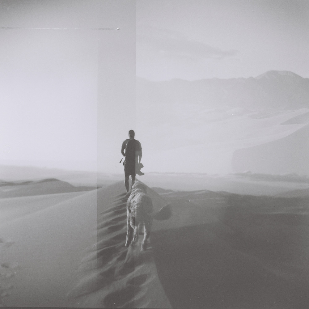 A black and white holga photo of photographer Justin Key and his dog Lambeau at the sand dunes